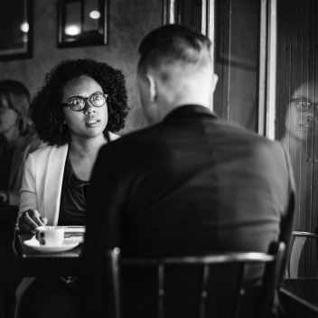man and woman talking to each other while sitting on chair